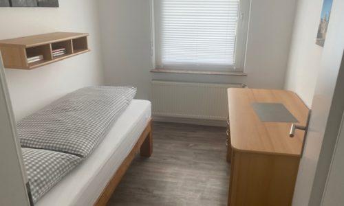 Kleines Schlafzimmer mit Schreibrtisch in der Ferienwohnung Heppenheim